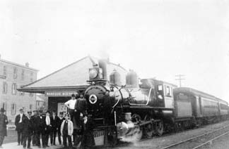 The Erie Railroad, Wanaque-Midvale Station, as a crowd gathers around the mode of the day.